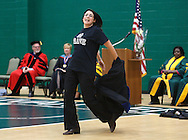 "SUNY Sullivan President Karin Hilgersom takes off her academic robe as she and other staff and faculty do a flash mob to ""Brave"" by Sara Bareilles during convocation in the fieldhouse on Monday, Sept. 9, 2013."