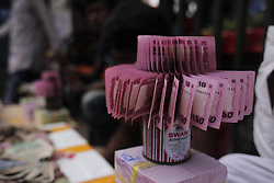 May 24, 2019 - Dhaka, Bangladesh - Street vendor displays new banknotes for exchange on commission as people buy to distribute to the younger member of the family and to the poor at the end of the Ramadan on the Eid-al Fitr, the greatest Muslim religious festival of the year near a street in Dhaka. The vendor keeps two percent commission. (Credit Image: © MD Mehedi Hasan/ZUMA Wire)