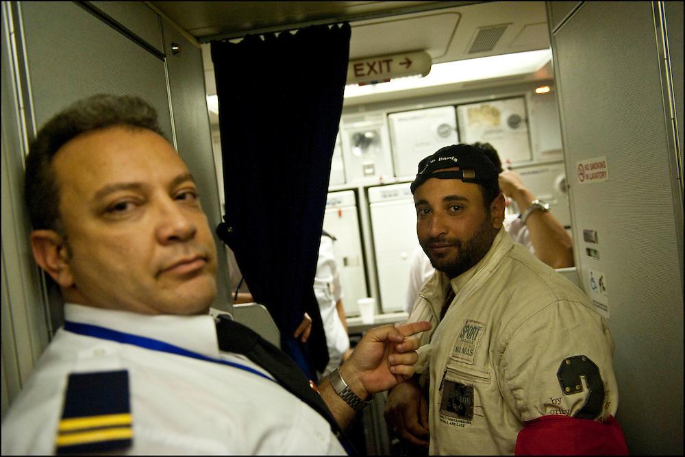 (sur la droite) Ahmed El Fayed 27 ans originaire de Tanta en Egypte, ouvrier dans le Batiment en Libye a fui vers la Tunisie quand son patron lui a rendu son passeport avant de prendre la fuite vers une destination étrangère. Seule explication laissée:  les mois de Janvier et de Février ne seront pas payés. Dans l'avion qui le ramène au Caire. © Benjamin Girette/IP3 press