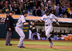 April 5, 2010; Oakland, CA, USA;  Seattle Mariners right fielder Ichiro Suzuki (51) celebrates with catcher Rob Johnson (32) after scoring a run against the Oakland Athletics during the ninth inning at Oakland-Alameda County Coliseum. Seattle defeated Oakland 5-3.