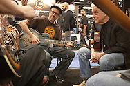 January 21, 2016 - Anaheim, CA: World touring US bluesmen Doug Macleod (at right - black jacket, jeans) and Nathan James (at left - hat, glasses) at the National Resophonic booth during the NAMM Show, an annual trade show organized by the The National Association of Music Merchants (NAMM). <br /> <br /> The largest of its kind, NAMM features music instruments and products of every imaginable music-related item. National Resophonic was started in 1989 by Don Young and McGregor Gaines in a garage in Long Beach, CA. The two resurrected the legendary guitar company National String Instrument Corporation originally founded in 1927 by the Slovakian born John Dyoperra. These instruments called &quot;resonator guitars&quot; were steel bodied with built in speaker cones that projected loud sound, good enough for live performances. Their unique sound became the preferred instrument of blues, Hawaiian and hillbilly musicians of the 1930s and are iconic of these musical genres. National went out of business in the 1950s due to the invention of the electric guitar. In 1990, Young and Gaines formed National Resophonic, a new company in San Louis Obispo, CA that produced excelent modern versions of the older guitars. Their guitars are in very high demand worldwide among guitarists from street performers to famed musicians like Keb' Mo', Bonnie Raiit, John Mellencamp and Eric Clapton. National currently produces nearly 2700 instruments per year, representing more than 50 different models. The waiting list to order one of their guitars can be several months. Young and Gaines sold their interests in the company which it is now owned by Eric Smith, an emplyee of National for 24 years. Sadly, Don Young passed away on June 15, 2016. (Torin Boyd/Polaris).