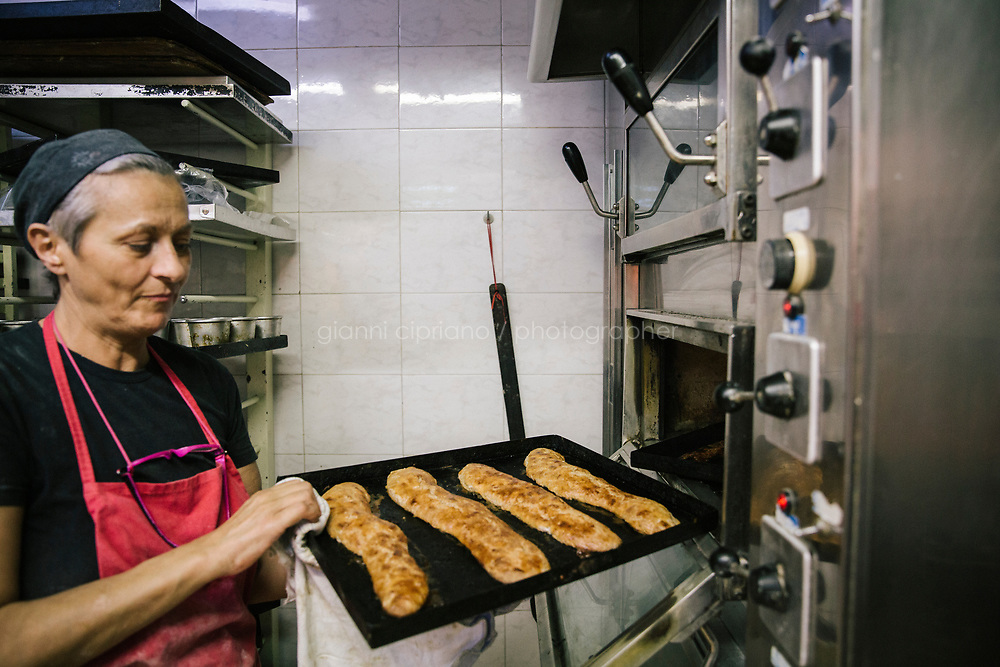 NAPLES, ITALY - 7 JUNE 2018: Lucia Tagliatela pulls a tray of quaresimale cookies out of the oven here at Pasticcielo, a bakery in Naples, Italy, on June 7th 2018.<br /> <br /> Pasticciello was founded 34 years ago by Lucia Tagliatela.