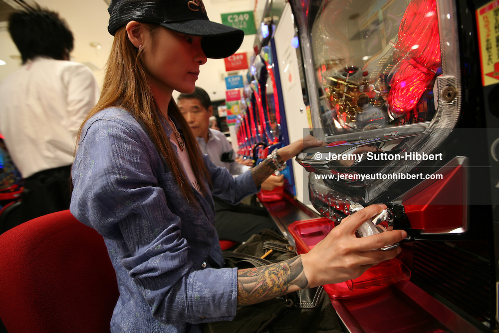 Revealing her Yakuza style tattoos on her arms, Shoko Tendo sits in the 'pachinko' gaming parlor where she used to work, in Sugamo district of Tokyo, Japan, Friday, Aug. 31st, 2007. Shoko Tendo, daughter of Yakuza boss Hiroyasu Tendo (now deceased) has written an autobiographical book - 'Yakuza Moon',  describing her life growing up with a Yakuza criminal boss for a father, of her addiction to drugs, and the failed, and often violent sexual relationships she had with men. Shoko Tendo lives in Tokyo with her 2 year old daughter Komachi.