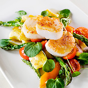 Scallops on a bed of fresh greens and vegetables