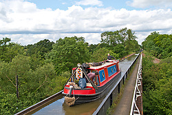 © Licensed to London News Pictures. 20/06/2019. Bearley, Warwickshire, UK. A passenger pets her dog as a barge crosses the Edstone Aqueduct during a warm and pleasant day in Warwickshire, UK. At 475 feet (145 m), Edstone is the longest cast iron aqueduct in England Photo credit: LNP
