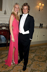 MISS POPPY DELEVINGNE and EDWARD LAWSON-JOHNSTON at a dinner hosed by Moet & Chandon at their headquarters at 13 Grosvenor Crescent, London on 12th October 2005.<br />
