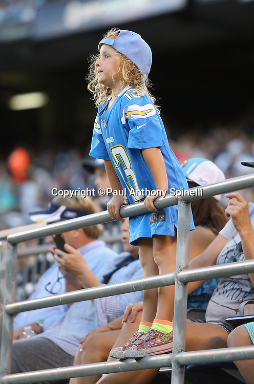 A young San Diego Chargers fan stands on a front row field level railing while dressed in a Chargers hat and jersey during the 2015 NFL preseason football game against the Seattle Seahawks on Saturday, Aug. 29, 2015 in San Diego. The Seahawks won the game 16-15. (©Paul Anthony Spinelli)