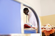 Doctor Ivan Nyenje examines a patient at Kasangati Health Centre in Uganda.