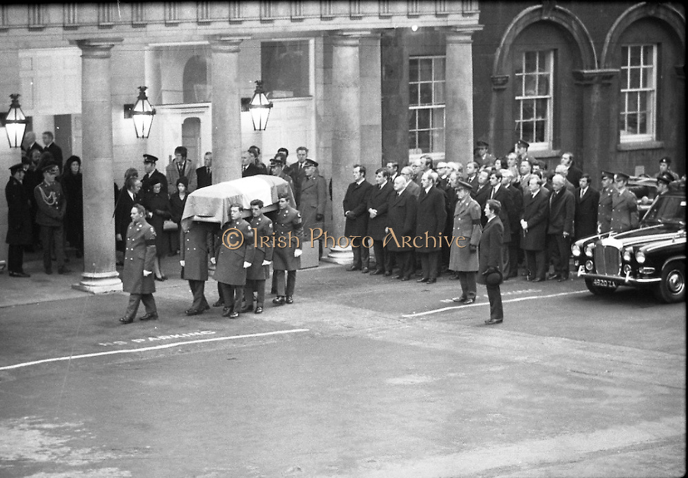 Funeral of President Childers.    (H62)..1974..20.11.1974..11.20.1974..20th November 1974..Following a period of lying in state, the remains of President Erskine Childers were removed today from Dublin Castle. The cortege would transfer the president to St Patrick's Cathedral where the funeral service would be held...Image shows the guard of honour carrying the coffin of President Childers to the waiting gun carriage. The Government ministers are seen standing to the right of the coffin.