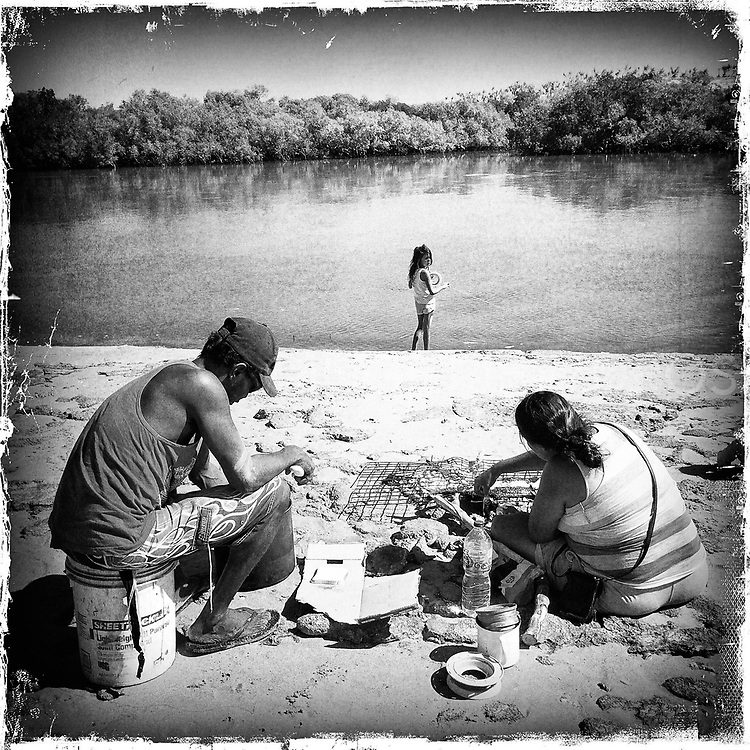 Jeremy and Melissa preparing freshly caught fish on the fire, while their daughter Taneisha is trying to catch more. Fishing is an important part of the cultural and economic life of Aboriginal people as it is a integral component of connection to their traditional country. Quite often the fish while be shared with other family members, especially the elderly. Beagle Bay community, Western Australia