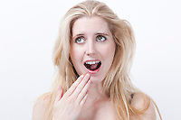 Surprised young woman with mouth open against white background