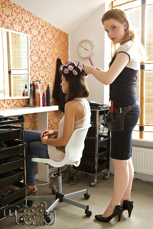 Female hairdresser adjusting curlers in young woman's hair