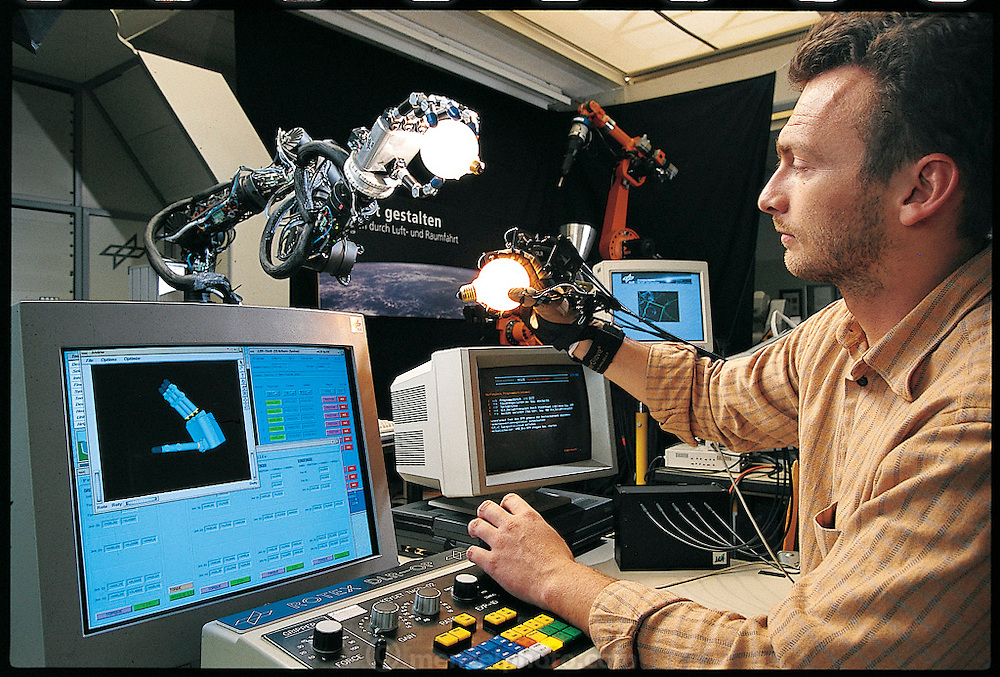 The robotic hand developed at the Deutsches Zentrum für Luft und Raumfahrt (German Aerospace Center), in the countryside outside Munich, Germany, demonstrates the power of a control technique called force-feedback. To pick up an object, Max Fischer (in control room), one of the hand's developers, uses the data-glove to transmit the motion of his hand to the robot. If he moves a finger, the robot moves the corresponding finger. From the book Robo sapiens: Evolution of a New Species, page 135.