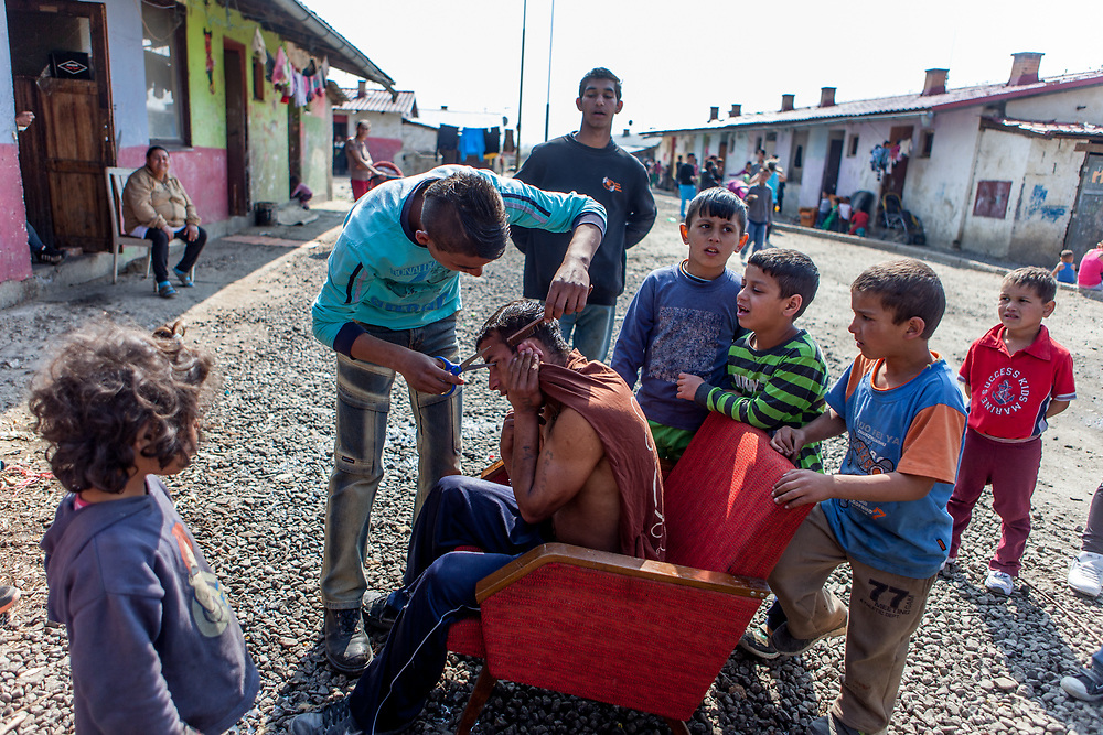 """A inhabitant of the Roma settlement in Moldava nad Bodvou is getting an outside haircut on the main road of the settlement """"Budulovska Street"""" located about 30 km from Kosice (2014). The city has roughly 11200 inhabitants, about 1980 (18%) of them have Roma ethnicity and around 800 are living at the segregated settlement 'Budulovska Street' (2014)."""