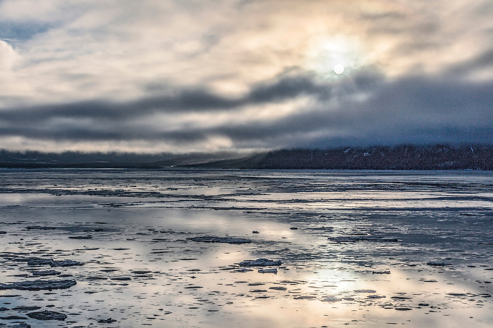 Alaska.  The sun near its zenith during winter solstice shining through clouds over Turnagain Arm near Hope on December 21, 2016 with its reflection in the ice-clogged water.  At this time of year the angle of the sun above the horizon in Anchorage is only 5.5 degrees.
