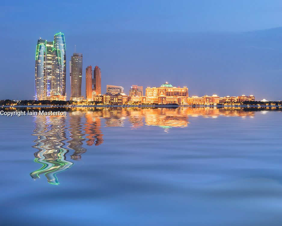 Evening skyline of Abu Dhabi reflected in sea in United Arab Emirates