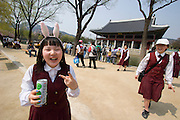 Gyeongbokgung Palace. Gyeonghoeru Pavillion. School girl with bunny ears.