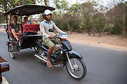 A Cambodian man drives two smiling Western tourists on his a motorbike Tuk Tuk along the road from Angkor region, Siem Reap Province, Cambodia, South East Asia. (photo by Andrew Aitchison / In pictures via Getty Images)