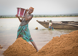 © Licensed to London News Pictures. 05/07/2013. Koulikoro,  Mali.  Balas (13) will spend 8 hours a day dredging sand which has been dropped by the workers. The sand is transported to the shore which is then delivered across Mali for use within the construction industry.   Photo credit: Alison Baskerville/LNP