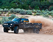 Black dodge truck spinning in the sand dunes. Flog Industries truck