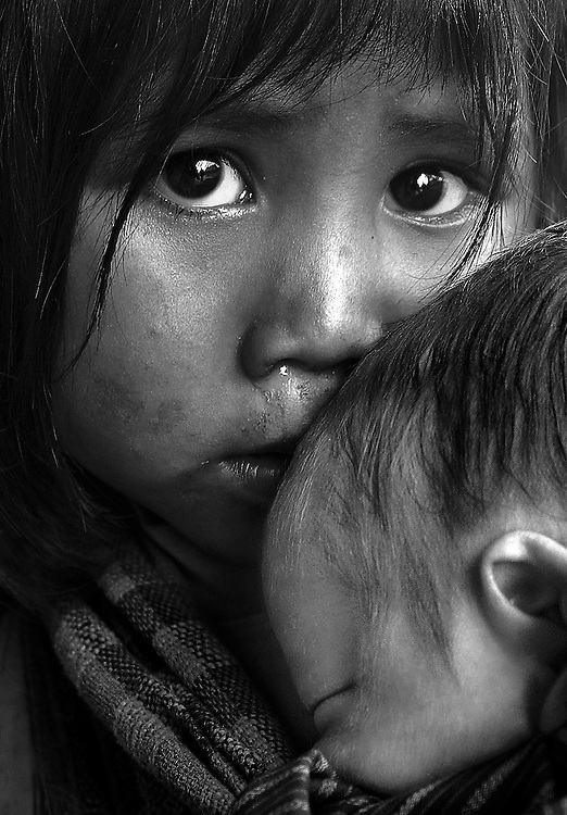 A poor village girl cares for her sister in northern Laos.