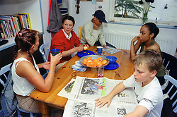 Two family groups sitting at table in kitchen talking,