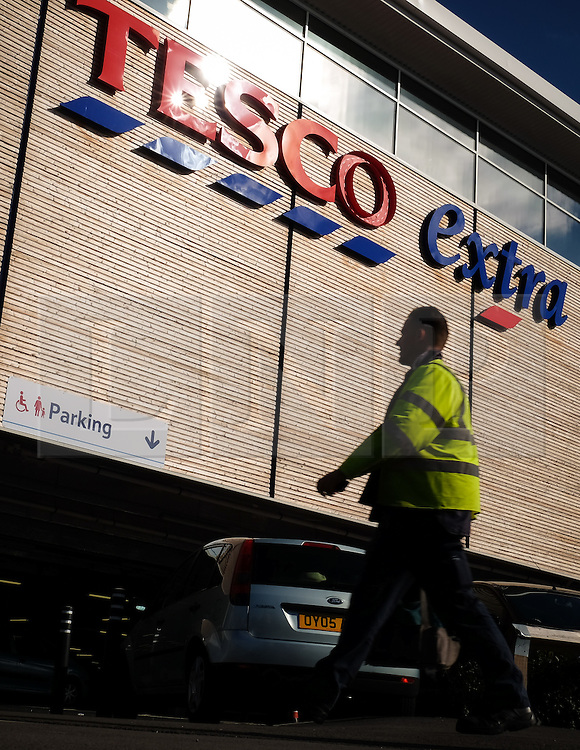 © Licensed to London News Pictures. 05/10/2016. Portsmouth, Hampshire, UK.  A man walking past a Tesco Extra in Portsmouth this morning. Tesco PLC, Britain's largest supermarket chain has announced that like-for-like sales had grown in the first half of its financial year. The results come following increased competition in the market from budget supermarkets such as Aldi & Lidl. Photo credit: Rob Arnold/LNP
