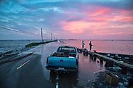 Fishing on Island road after Hurricane Barry flooding Isle de Jean Charles.