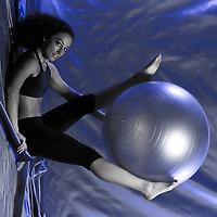 young woman exercising swiss ball studio