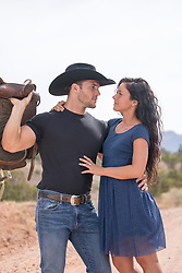 hot cowboy holding a saddle and a girl outdoors