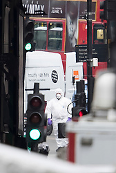 © Licensed to London News Pictures. 04/06/2017. London, UK. A policeman in a protective suit is seen next to a van believed to have been driven by the attackers - after an attack by three men killed seven and injured at least 48. Police shot three attackers dead after they deliberately drove their van at people on London Bridge and then stabbed drinkers at bars in nearby Borough Market. Photo credit: Peter Macdiarmid/LNP