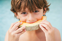 Boy (7-9) eating slice of melon close-up