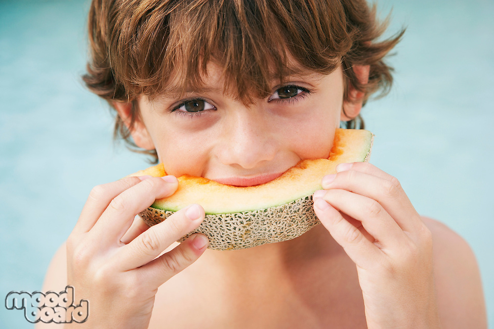 Boy (7-9) eating slice of melon close-up