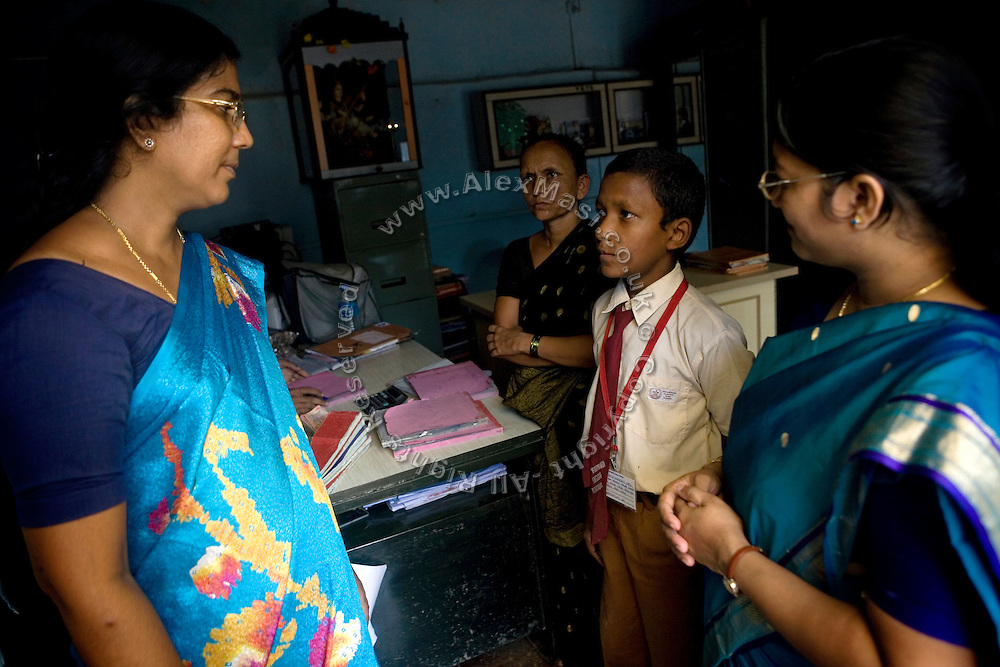 .A child has been called with his mother in the teacher's office to discuss some matters over his studies at a school run by Sonrisas de Bombay, a fast-growing Spanish NGO in Mumbai, India..
