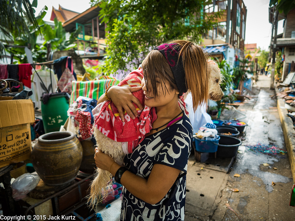 16 NOVEMBER 2015 - BANGKOK, THAILAND:  A woman being evicted from her home carries her dog through the Wat Kalayanamit neighborhood. Fifty-four homes around Wat Kalayanamit, a historic Buddhist temple on the Chao Phraya River in the Thonburi section of Bangkok, are being razed and the residents evicted to make way for new development at the temple. The abbot of the temple said he was evicting the residents, who have lived on the temple grounds for generations, because their homes are unsafe and because he wants to improve the temple grounds. The evictions are a part of a Bangkok trend, especially along the Chao Phraya River and BTS light rail lines. Low income people are being evicted from their long time homes to make way for urban renewal.          PHOTO BY JACK KURTZ