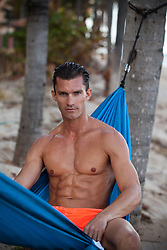 good looking man at the beach in a hammock