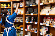 Member of staff stacking chocolates on display in the famous Dallmayr food store in Munich, Bavaria, Germany