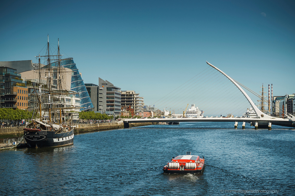 Dublin, May 2013: The dublin Tourist boat travels along the river liffey in the bright may sunshine as tourists walk alng the river banks
