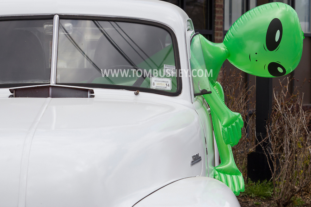 Pine Bush, New York - An inflatable alien sticks out of a pickup truck at the Pine Bush UFO Fair on  on April 26, 2014.