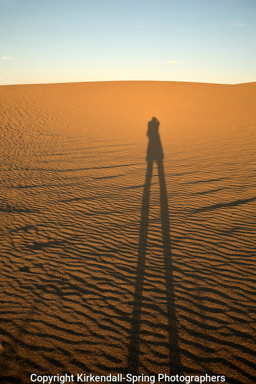 ID00647-00...IDAHO - Hiker on the sand dunes at sunset in Bruneau Dunes State Park.