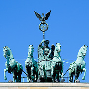 Quadriga Statue of Roman Goddess of Victory Victoria atop Brandenburg Gate in Berlin, Germany.