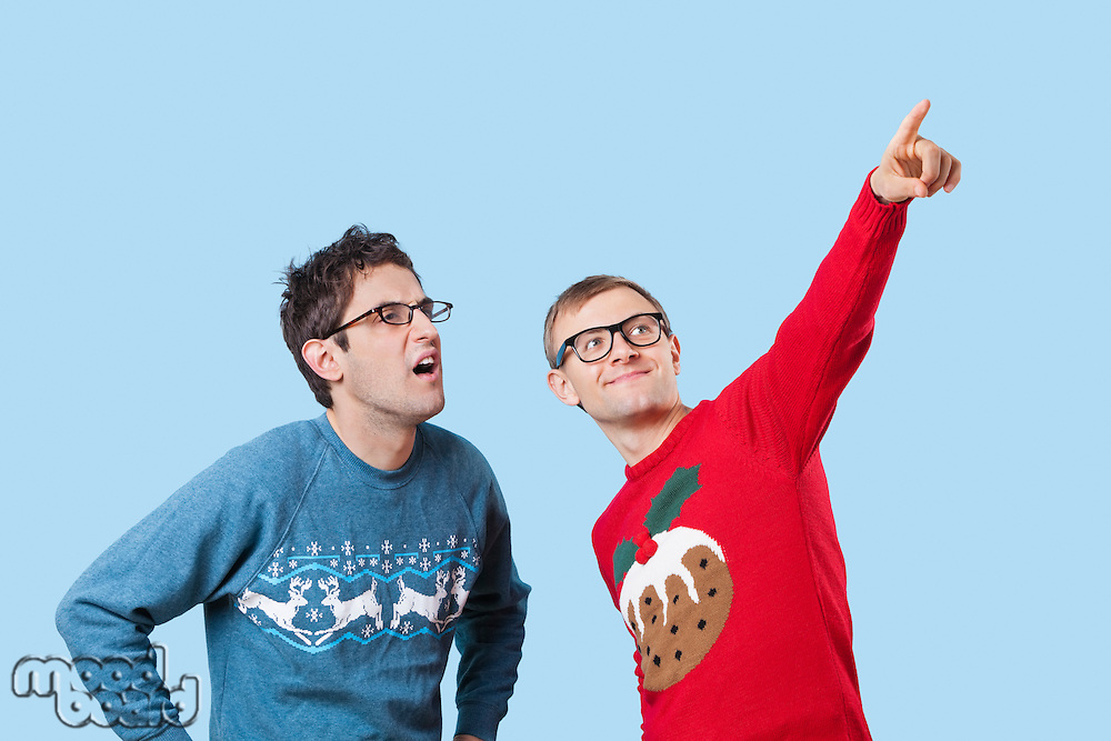 Two young men looking up against blue background