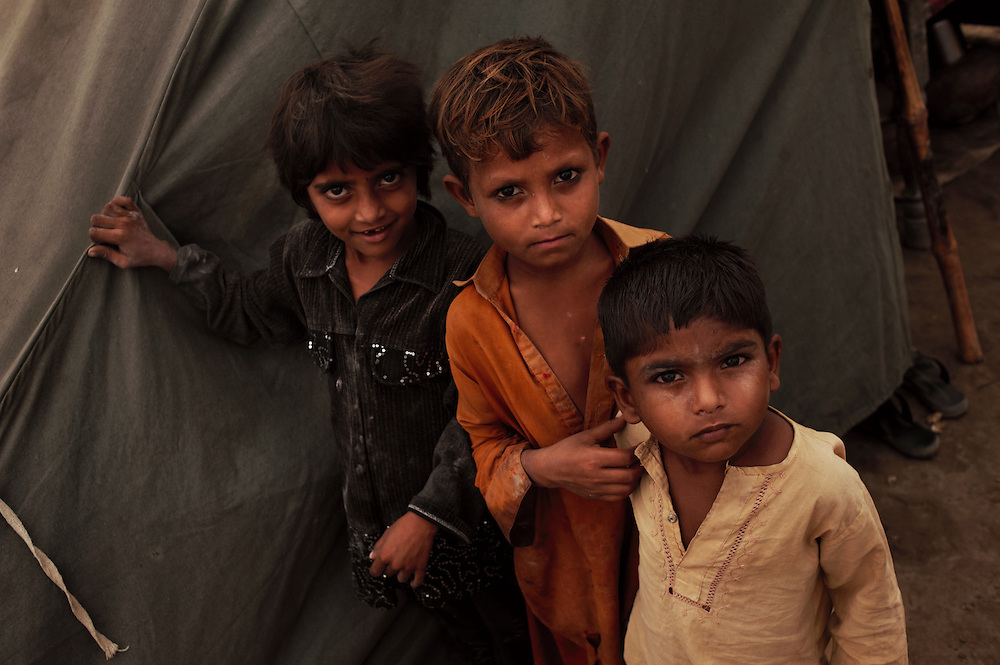 Boys stand by a tent within in a temporary camp at Digri Bypass in Mirpur Khas district, Sindh, Pakistan on November,  2011. In August 2011, Heavy monsoon rains triggered flooding in lower parts of Sindh and northern parts of Punjab
