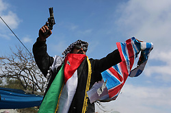 January 29, 2018 - Gaza City, Gaza Strip, Palestinian Territory - A Palestinian demonstrator gestures as he holds representations of Israeli, British and U.S. flags before burning them during a protest against a U.S. decision to cut aid, in Gaza City January 29, 2018  (Credit Image: © Ashraf Amra/APA Images via ZUMA Wire)