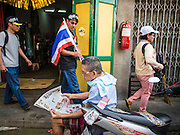 05 JANUARY 2014 - BANGKOK, THAILAND: A man reads his newspaper as anti-government protestors walk past him in Chinatown in Bangkok. Suthep Thaugsuband, leader of the anti-government protests in Bangkok, led the protestors on a march through the Chinatown district of Bangkok. Tens of thousands of people waving Thai flags and blowing whistles gridlocked what was already one of the most congested parts of the city. The march was intended to be a warm up to their plan by protestors to completely shut down Bangkok starting Jan. 13.     PHOTO BY JACK KURTZ