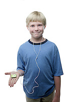 20 July 2008:  Back to School with grammar school Lytle brothers in Huntington Beach, CA.  Alex Lytle age 10 holding a green ipod shuffle wearing a blue shirt and white ear phones in the studio on white seamless paper silo.