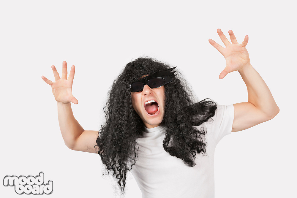 Portrait of young man with wig and sunglasses shouting against gray background