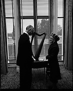 """Presentation of Harp to President DeValera..1972..29.12.1972..12.29.1972..29th December 1972..Mrs Julia Fennell presented a harp to President DeValera as a gift to Áras an Uachtaráin. She presented the harp on behalf of her late husband Mr Thomas J Fennell and herself..The harp was manufactured in 1835 at the firm of Robinson and Russell,westmoreland Street,Dublin. the harp is 36ins high and has 33 strings. It will be retained in an exhibition case bearing the inscription """"Tomas O'Fionnghaill agus Sile Ui Fhionnghail,Baile Atha Cliath, a bhronn ar Áras an Uachtaráin,1972"""".(Presented to Áras an Uachtaráin by Thomas and Julia Fennell,Dublin 1972)..Picture shows President DeValera positionong the harp in a prominent position within Áras an Uachtaráin. Mrs Fennel looks on approvingly."""
