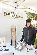"Artist Jodi Miller smiles while standing at her jewlery booth ""Beautiful Words"" during the Thousand Springs Art Festival at Ritter Island near Hagerman, Idaho. VMR"