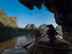 Asia, Vietnam, Van Long Nature Reserve. Tourists in boats exploring water filled cave.